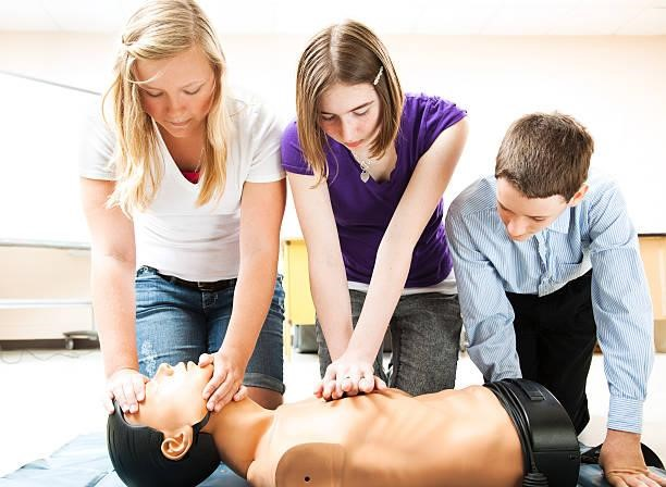 Family practicing CPR on test dummy