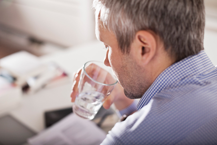 Mature businessman drinking water